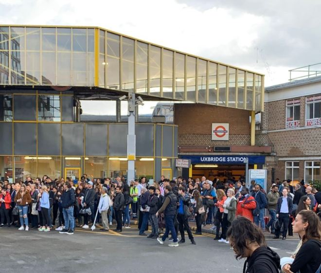 Commuters stand outside station after a man was stabbed during rush hour in West London