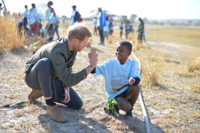 Prince Harry high-fives a young boy as he tours the Chobe Tree Reserve in Botswana today