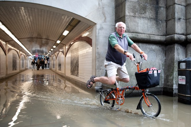 A cyclist tries to stay dry in a flooded tunnel at Blackfriars, London