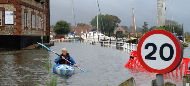 A cannoest paddels down a high street on a Norfolk coastline as flood alerts have been issued for today