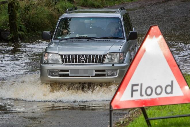 A motorist drives their car through floodwater in Birmingham