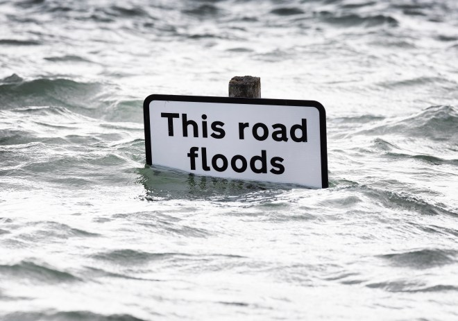 A sign that reads 'This road floods' is almost completely submerged in West Sussex