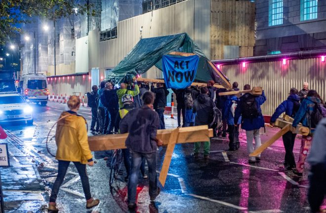 Extinction Rebellion environmental activists walk away under a tent structure after Police threatened to take it from at a site