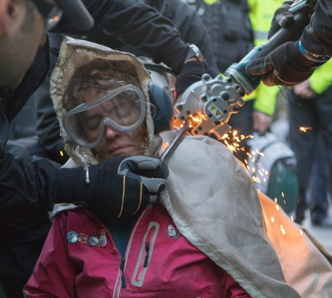 Police try to cut a woman chained to other eco-warriors in Whitehall this evening