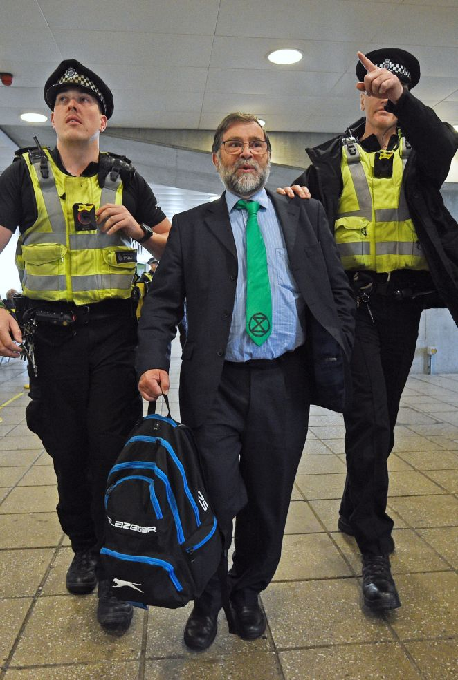 A man in an Extinction Rebellion tie is led away by officers