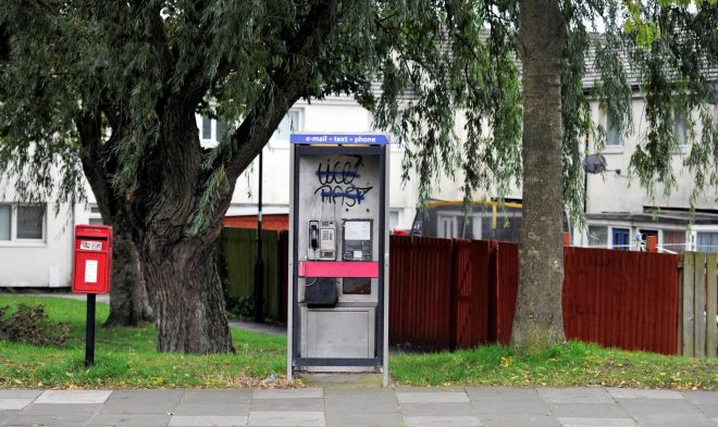 A telephone box is seen here covered in graffiti