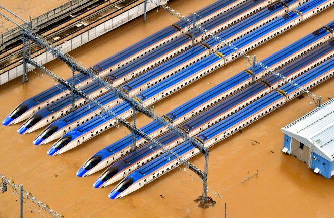 Bullet trains are pictured here submerged after the banks of Chikumagawa River in Japan collapsed