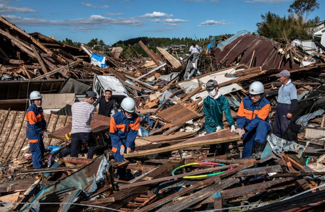 Search and rescue crews salvage belongings from the debris of buildings destroyed by a typhoon