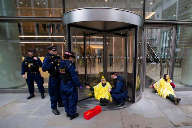 Protesters dressed as yellow canaries glued themselves to the entrance of the Walkie Talkie building