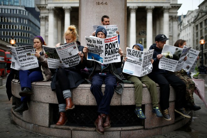 Protesters read mocked-up newspapers as they bring traffic to a standstill in the City of London