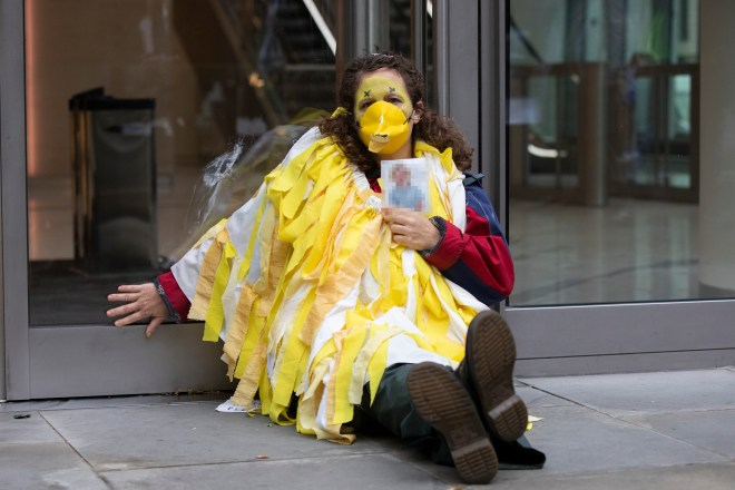 A woman with a yellow beak on her face sits glued to the office building in Fenchruch