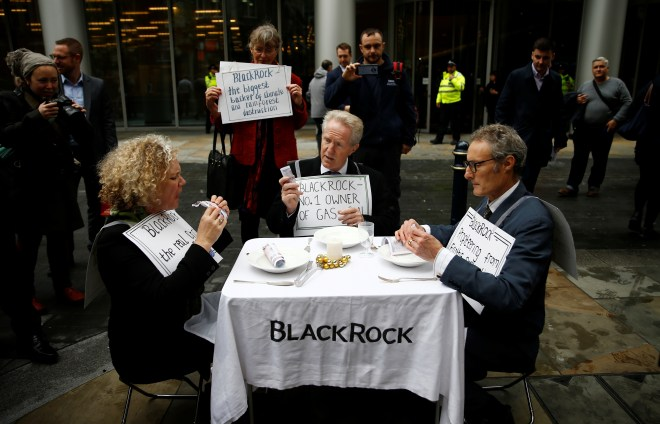 Protesters eat fake money outside the BlackRock office in the City of London