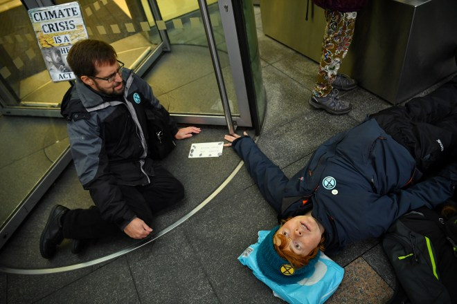 A protester lies on the ground after she glued herself to revolving door of Baclays Bank in Canary Wharf
