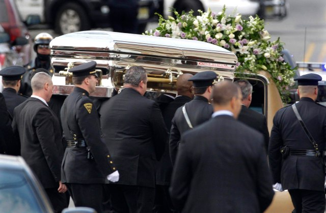Whitney's gold casket is carried to her final resting place