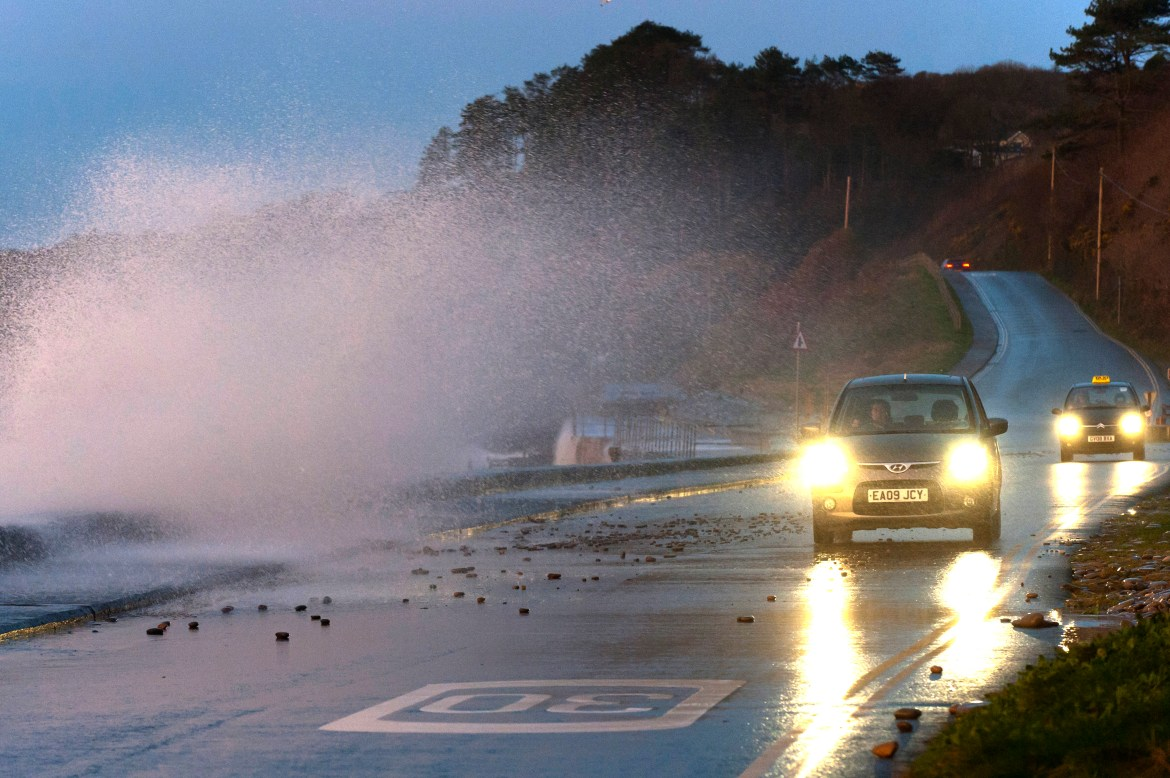 UK weather forecast: sea spray travels a car while a driver makes his way carefully along the south-west coast of Wales