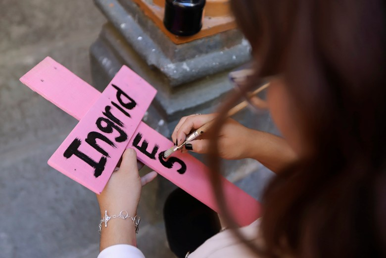 A woman paints the name of Ingrid Escamilla on a wooden cross to pay tribute after the gruesome murder