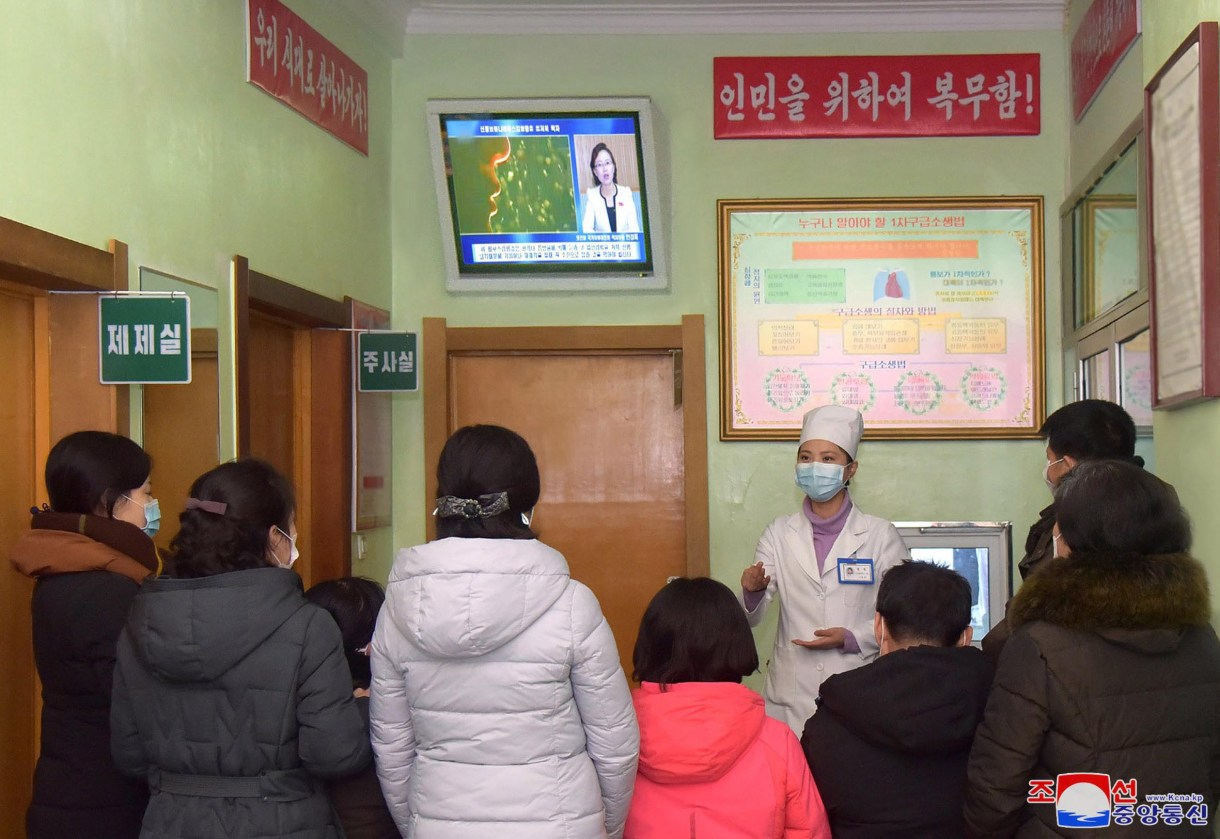 A health worker speaks to people about coronavirus, in Pyongyang