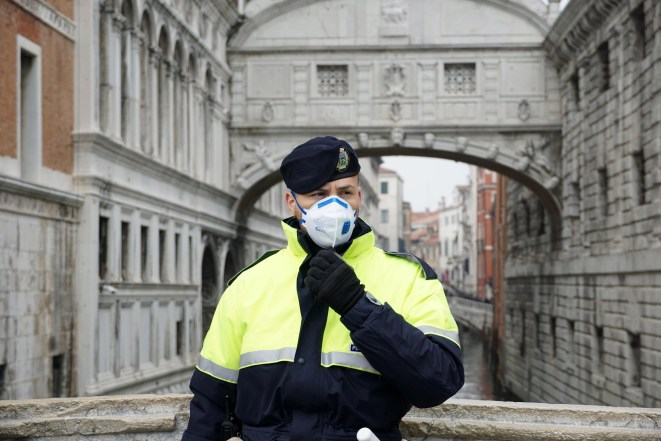 A cop in Venice wears a protective mask as the city's carnival is shutdown over coronavirus fears