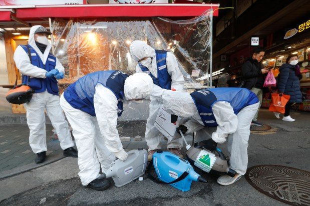 Workers wearing protective gears prepare to spray disinfectant as a precaution against the coronavirus at a market in Seoul