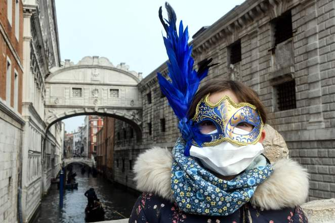 A young tourist wearing a protective face mask and a Carnival mask visits the streets of Venice