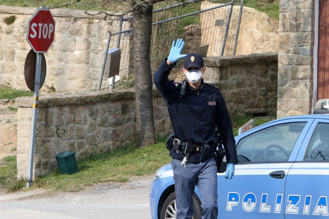 A cop enforces a blockade at the entrance of the small town of Vo' Euganeo, Padova
