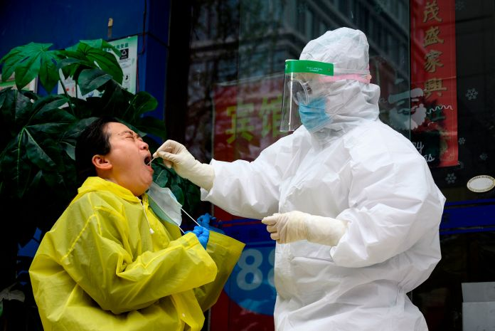 A medical worker wearing a hazmat suit dabs a woman to check if she has a coronavirus in Wuhan