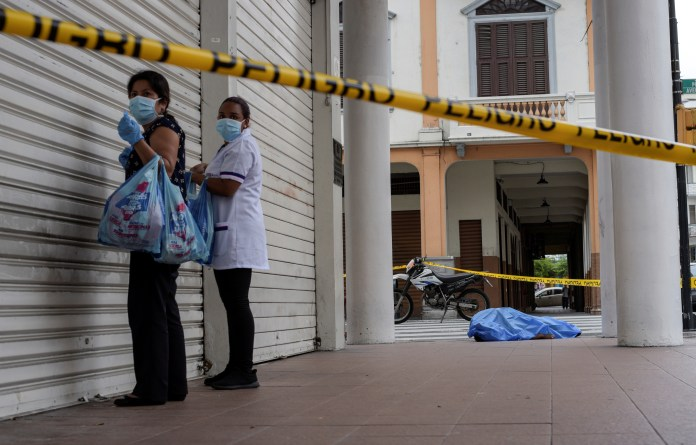 Women stand near the body of a man who collapsed in Guayaquil on March 30