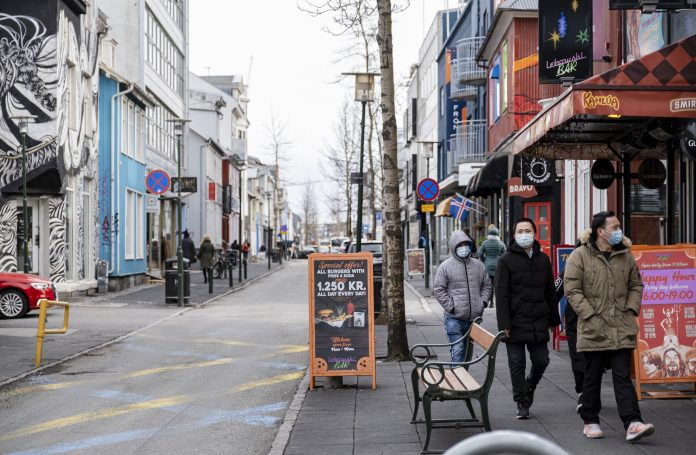 People with masks walk in downtown Reykjavik as the nation reports only seven deaths to date
