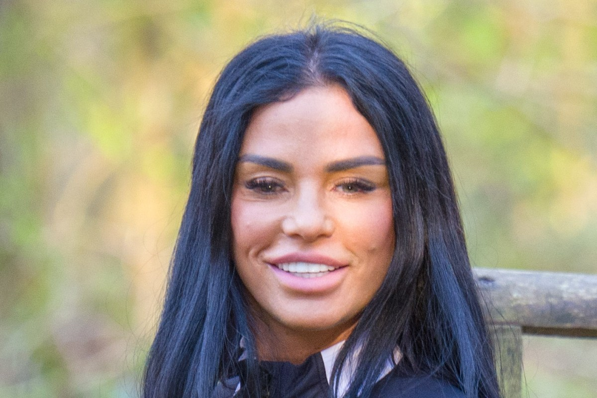 Katie Price is all smiles as she enjoys a walk with her dog Blade