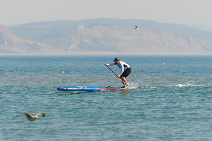 A paddle boarder on the water at Lyme Regis in Dorset on a hot sunny afternoon during the coronavirus lockout