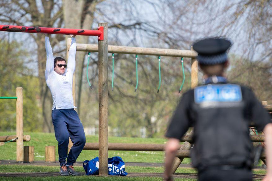 Un oficial de policía se acerca a un hombre que usa equipo de gimnasio público en un parque en Northampton, mientras la policía anuncia que está endureciendo su aplicación de distanciamiento social