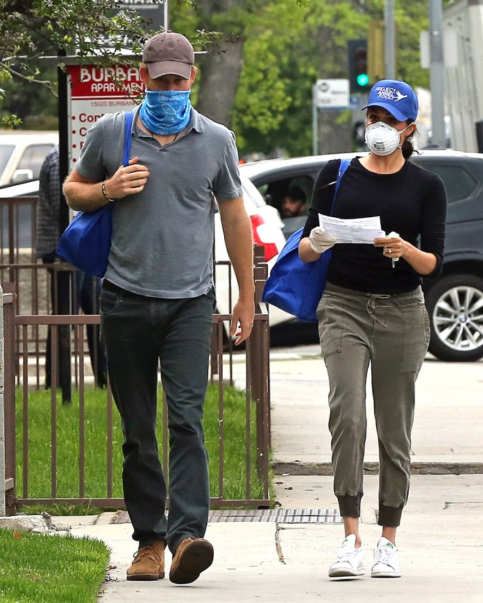 Harry opted for a blue bandana over his mouth and nose as he carried supplies from a blackened 4x4