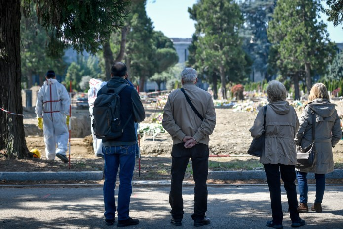 Mourners stood at the funeral at the Maggiore cemetery in Milan, Italy