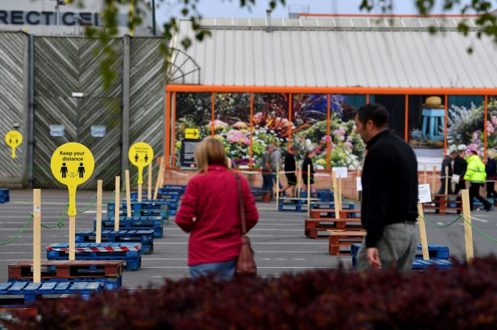 Customers line up in front of the B&Q warehouse, which has reopened after more than a month of closure, in Stoke-on-Trent, Staffordshire