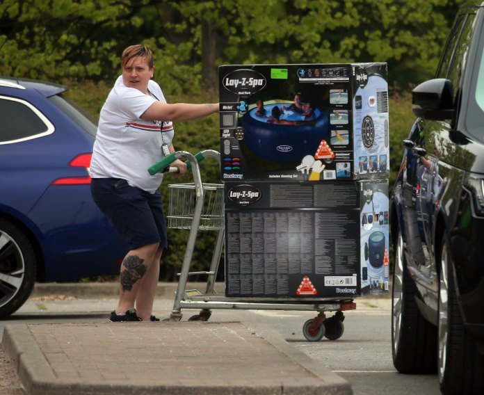 A customer carries items from Homebase to Harrogate after the store reopens
