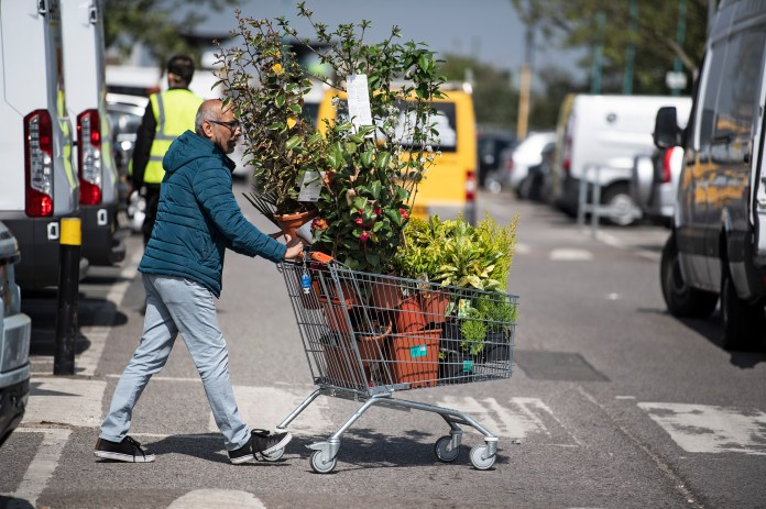 Man leaves B&Q store with certain products after reopening of certain stores