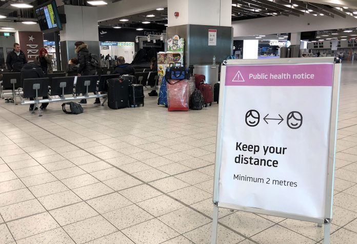 Airport notices are in place to keep passengers at a safe distance