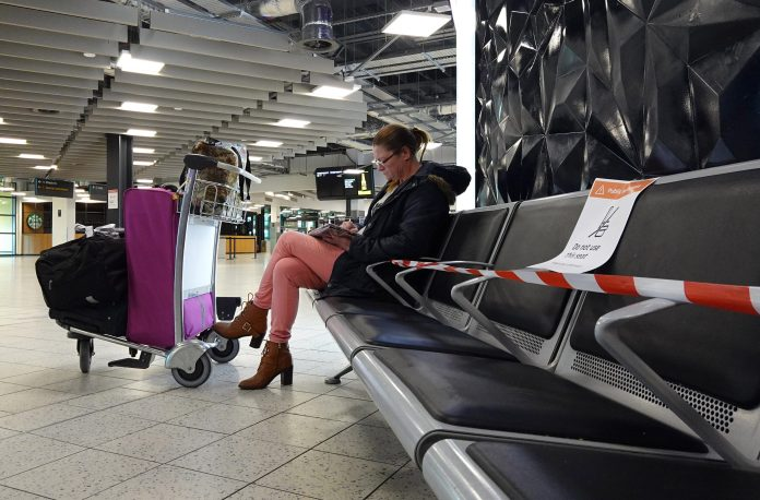A passenger waits on seats that have been locked up at the airport