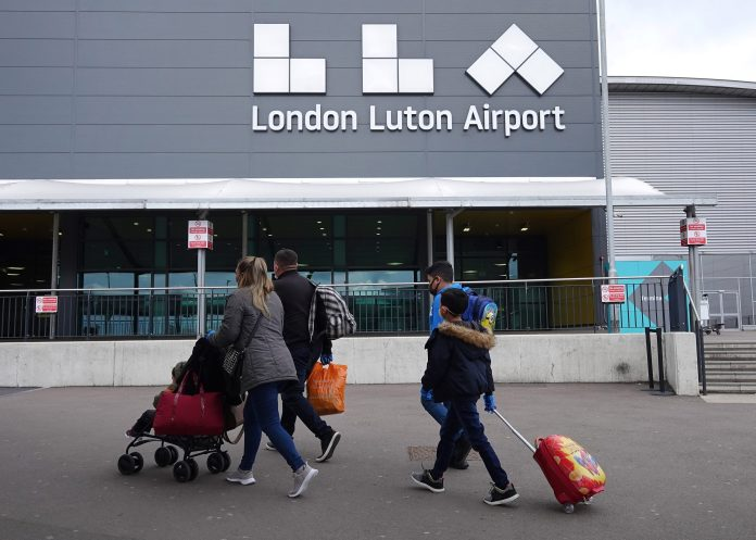 A family enters Luton Airport as they take one of the first flights outside the country with Wizz Air