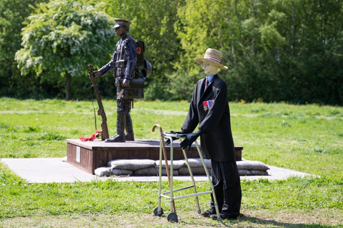 A tribute to Colonel Tom Moore stands next to a war memorial in Merseyside