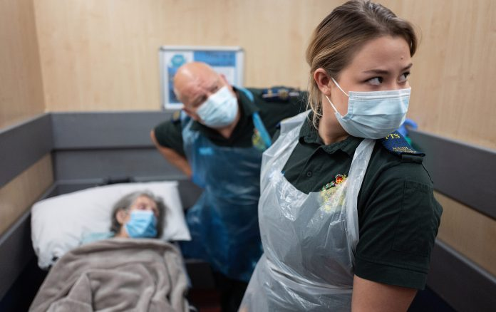 Paramedics are seen in masks to treat an elderly woman as the nursing home crisis becomes central