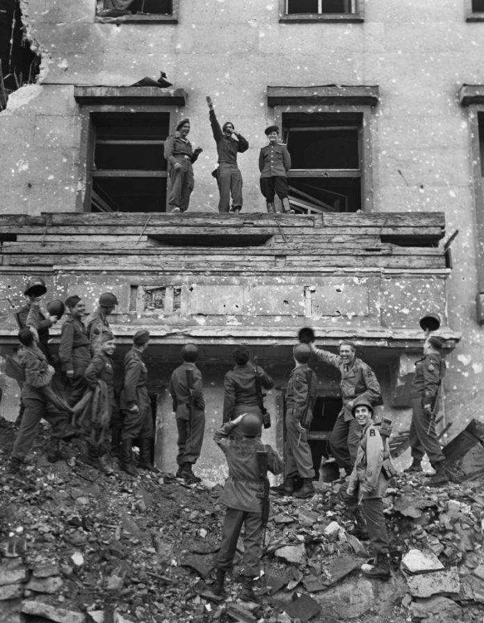 Corporal Russell M. Ochwad, from Chicago, mocked Adolf Hitler and made the Nazis salute on the balcony of Chancellor Reich in Berlin while American and Russian troops supported