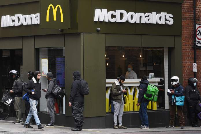 Delivery runners line up in front of a McDonald's in East London after the restaurant opens for delivery orders only