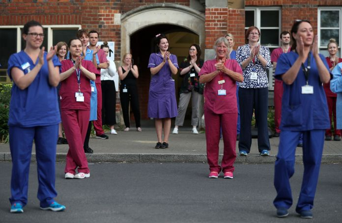 Hospital staff stands outside the Royal Hampshire County Hospital, to join in the applause to greet local heroes last night