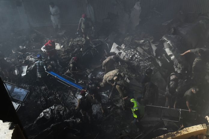Authorities sift through the smouldering wreckage searching for bodies