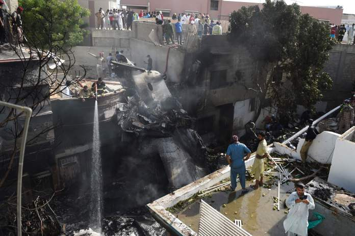 Smoking wreckage from the crash is seen in the packed residential area of Model Colony