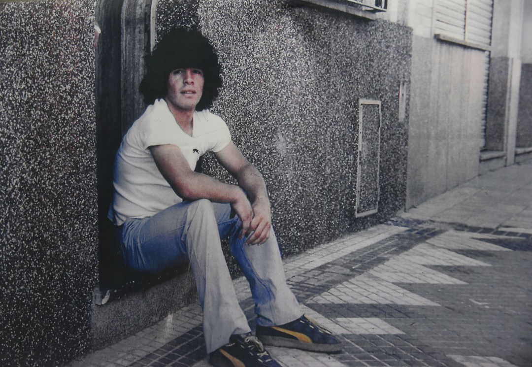 A teenage Maradona poses on the steps of his former home