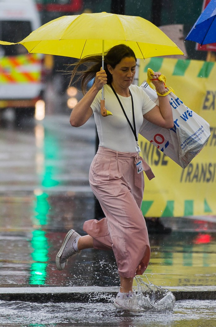 A woman avoids torrential rain at London's Parliament Square in Westminster
