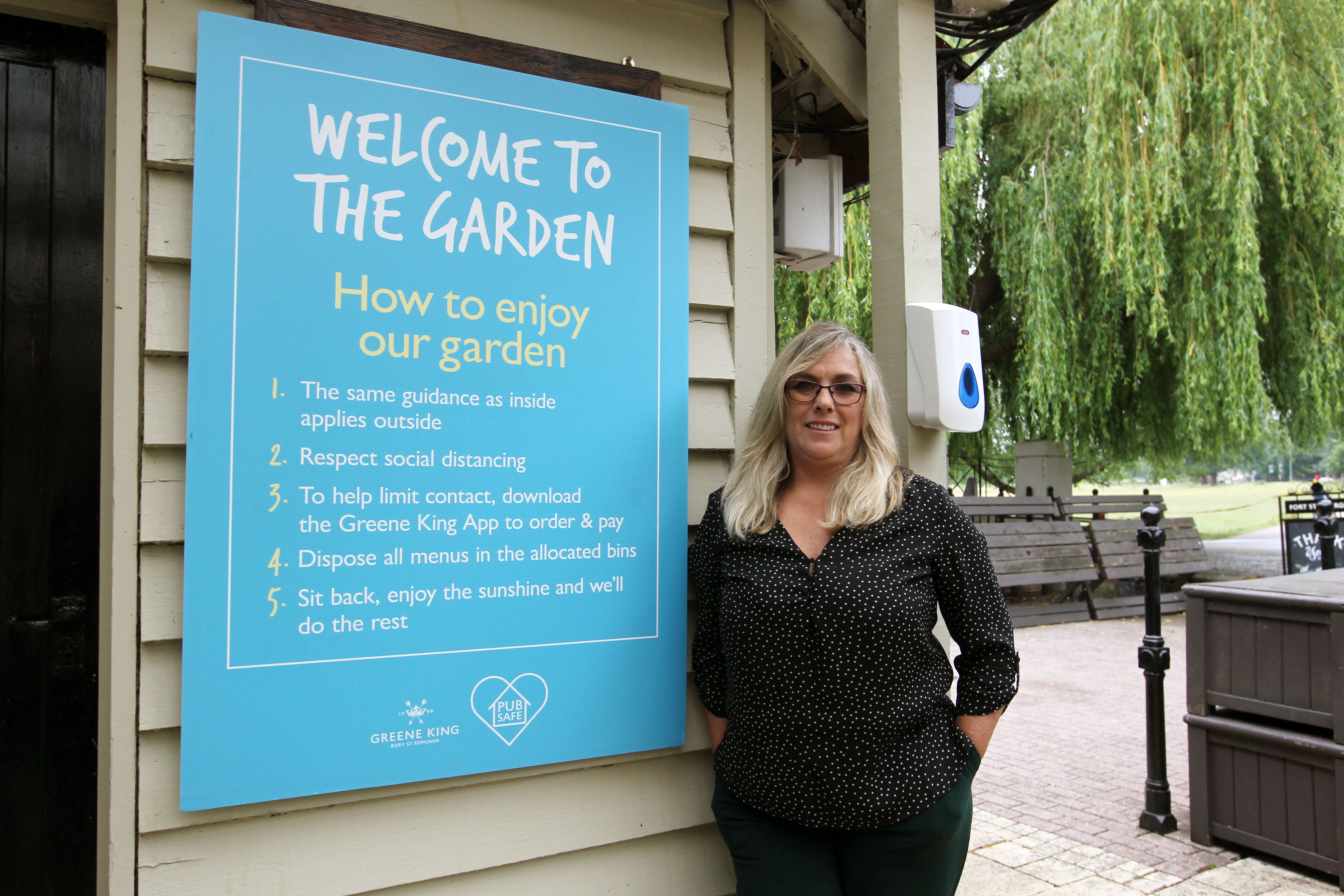 Sheree Thomas, general manager at the Green King Pub, Fort St George, stands next to the list of pub garden rules after the first lockdown