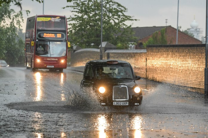 Taxi crosses large puddles as Met Office predicts more rain